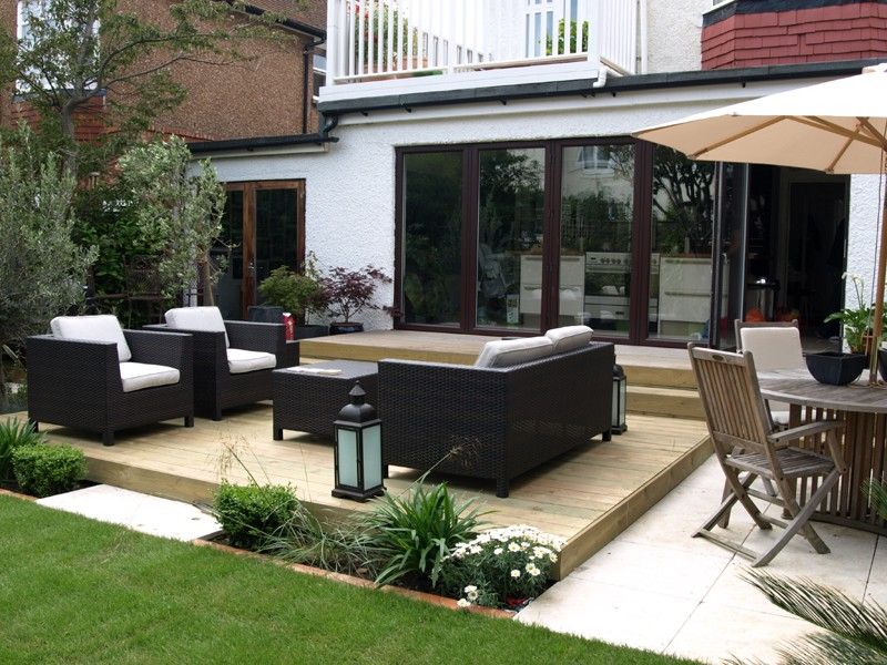 rattan furniture on the raised deck area - Garden Design Uk