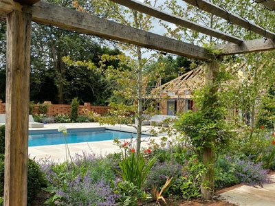 Oak pergola in Sussex Garden Design. Summerhouse design. Swimming pool. Paved terrace. Trees from Griffin Nurseries. Planting Design. Garden designer Sussex